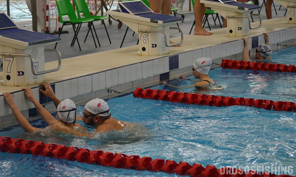 """Ο Φλουρής Χατζηγεωργίου ετοιμάζεται να ρυμουλκήσει τον συναθλητή τους Γιώργο Γάγκο στο αγώνισμα 4x50μ Κολύμβησης και 50μ Ρυμούλκησης. Στο βάθος διακρίνεται η Διουνσία Κάρδαρη που περιμένει την συναθλήτριά της για να την """"σώσει""""."""
